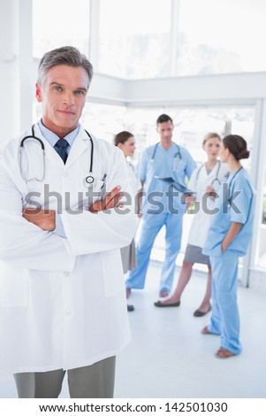 Doctor with arms folded standing in front of his medical team - stock photo