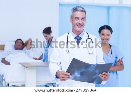Doctor with colleague and patient behind - stock photo