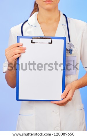 Doctor with copyspaced clipboard waist-high portrait on blue - stock photo