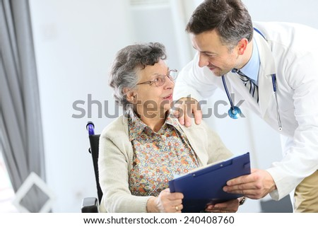 Doctor with elderly woman in nursing home