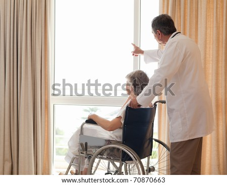 Doctor with his patient looking out the window - stock photo
