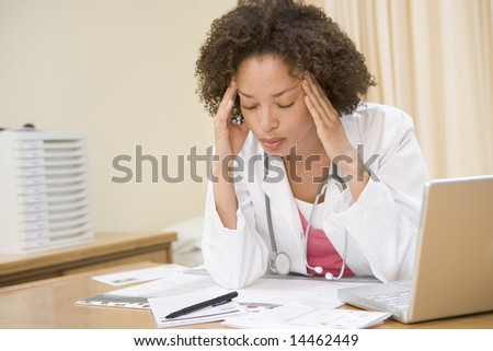 Doctor with laptop and headache in doctor's office - stock photo