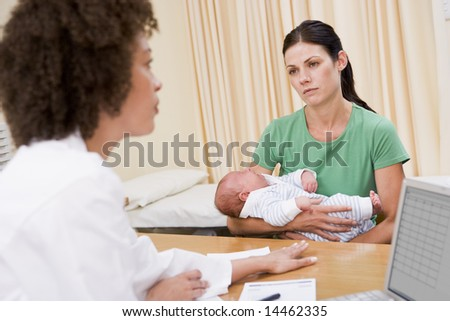 Doctor with laptop and woman in doctor's office holding baby - stock photo