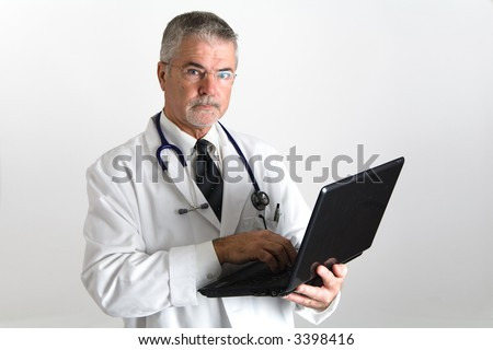 Doctor with laptop looking at the camera with a laptop in his hands