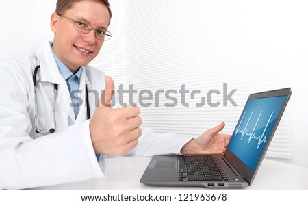 Doctor with laptop sitting in doctor's office and showing his thumb up - stock photo