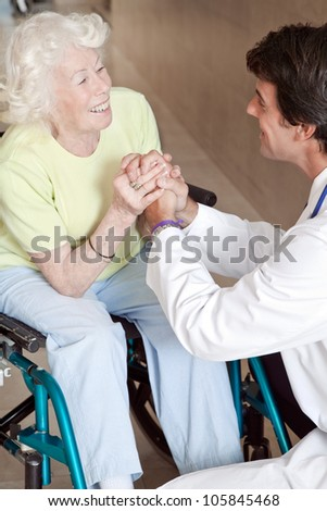 Doctor with patient on wheel chair at hospital.