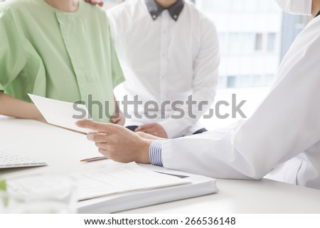 Doctor with patient pregnant woman and her husband - stock photo