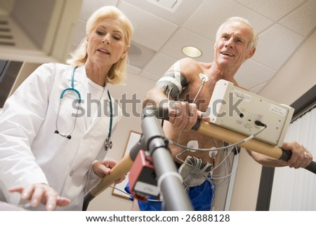 Doctor With Patient While They Run Being Monitored - stock photo