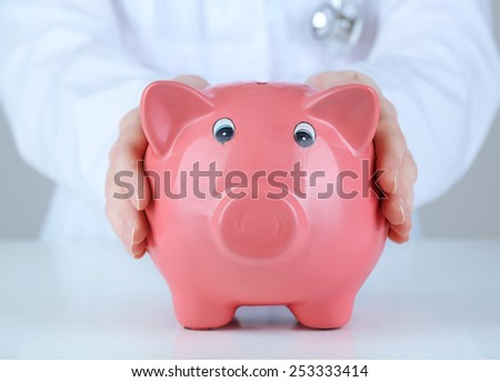 Doctor with pink piggy bank on grey background, close up