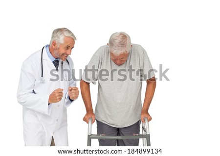 Doctor with senior man using walker over white background - stock photo