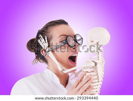 Doctor with skeleton against gradient  - stock photo
