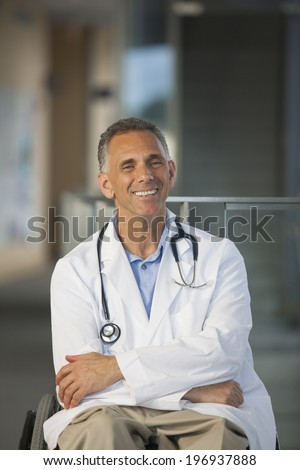 Doctor with spinal cord injury in a wheelchair wearing a stethoscope around his neck and a white lab coat