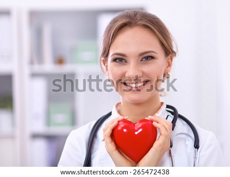Doctor with stethoscope holding heart, isolated on white  background - stock photo
