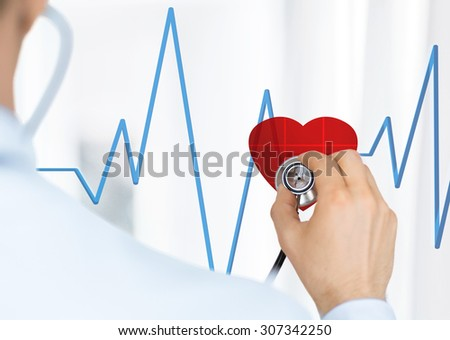 doctor with stethoscope listening heart beat on virtual screen - stock photo