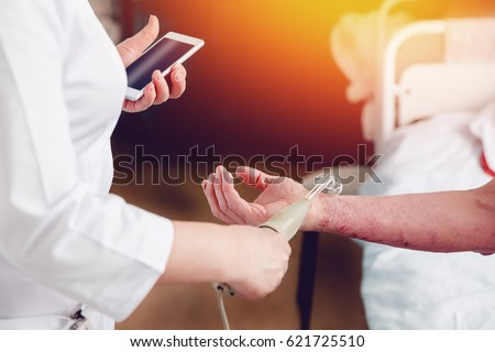 doctor with the phone treats a patient with a skin disease using the Darsonval apparatus for the treatment of dermatitis, apathic, seborrhea, eczema..high contrast