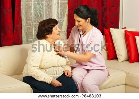 Doctor woman examine elderly patient in her home and sitting together on couch