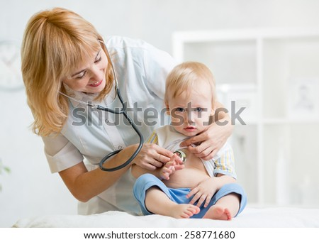 doctor woman examining heartbeat of little boy with stethoscope - stock photo