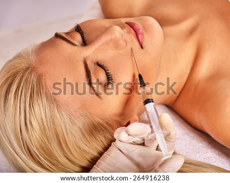 Doctor woman giving botox injections. Visible hand. - stock photo