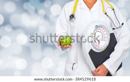 Doctor woman hands with scales and apple. - stock photo