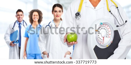 Doctor woman hands with scales and apple over health care background.