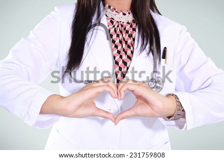 doctor woman showing hand-shaped love, isolated on green background - stock photo