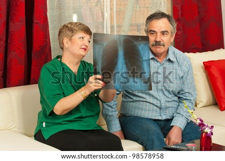 Doctor woman showing x-ray to senior man in his house - stock photo