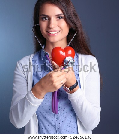 Doctor woman with stethoscope examining red heart