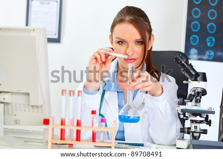 Doctor woman working with test tube in laboratory - stock photo