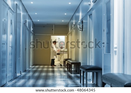 Doctor working at the end of a hospital hall - stock photo