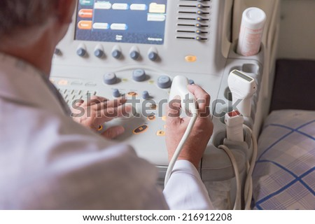 Doctor working for ultrasound machine - stock photo