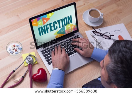 Doctor working on a laptop and INFECTION on his screen - stock photo