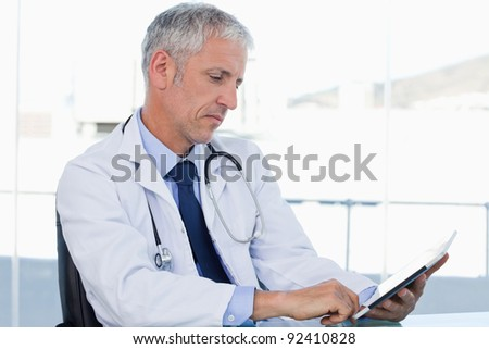 Doctor working with a tablet computer in his office - stock photo