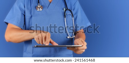 Doctor working with tablet computer on blue  background  - stock photo