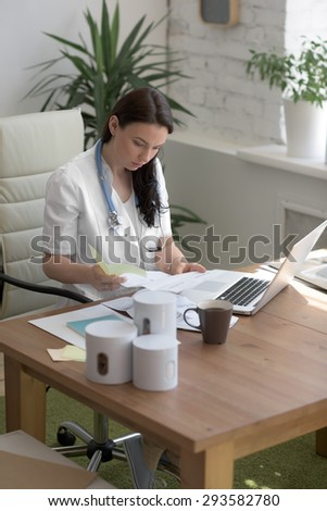 Doctor working with test results and computer at clinic. Filling patient medical record  - stock photo