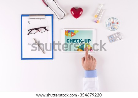 Doctor workplace with CHECK-UP on tablet screen - stock photo