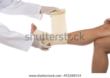 Doctor wrapping ankle of a woman with bandage isolated on white background.