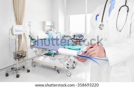 Doctor writing a medical prescription in hospital room - stock photo