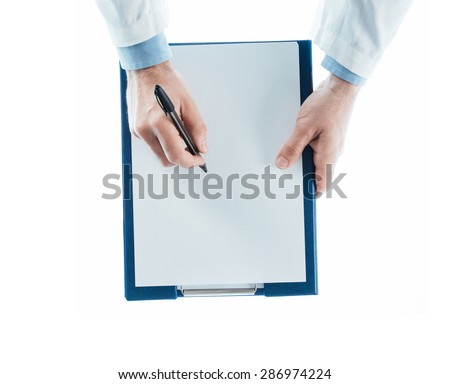 Doctor writing a prescription on a clipboard on white background, top view, hands close up - stock photo