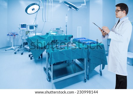 doctor writing clipboard for diagnosis in operating room of a modern hospital - stock photo