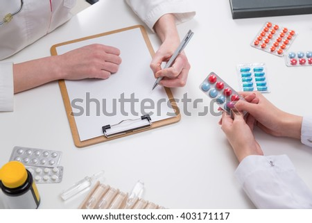 Doctor writing down prescription on desktop with colorful pills
