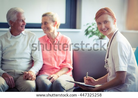 Doctor writing medical report of senior couple at home