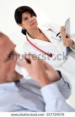 Doctor writing on a clipboard as her patient blows his nose - stock photo