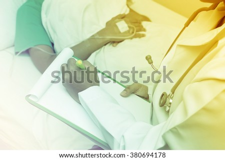 doctor writing on a medical chart with patient lying in a hospital bed - stock photo
