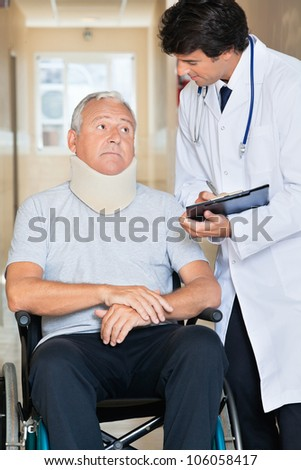 Doctor writing on clipboard while communicating with senior man sitting in wheel chair