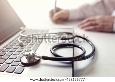 Doctor writing patient notes on a medical examination or prescription focus on stethoscope