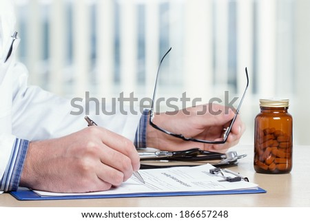 Doctor writing report in his office. - stock photo