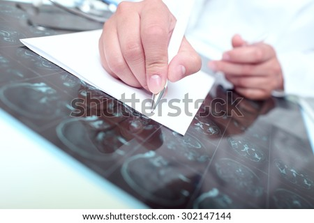 Doctor wrote on a paper examining the tomography scan of the patient - stock photo