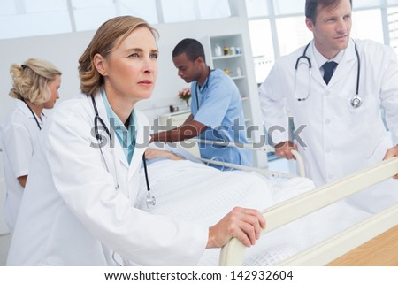 Doctors about to walk with patient bed in an emergency - stock photo