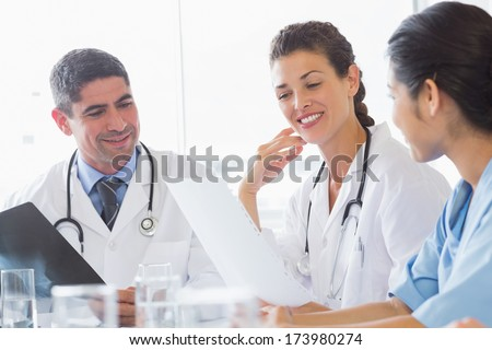 Doctors and nurse discussing over document in hospital - stock photo