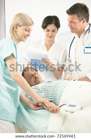 Doctors and nurse examining old patient in hospital, nurse measuring blood pressure, doctor taking notes.?